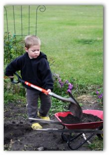 child shoveling dirt into a wheel barrow