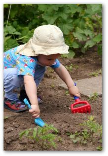 child gardening with a hand rake and trowel