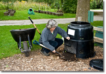gardener filling a wheel barrow with compost from a compost bin
