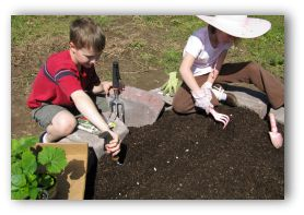 two young gardeners planting seeds in the ground