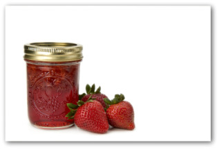 strawberry  jam in jar next to fresh strawberies