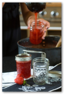 cook pouring strawberry jam into jars