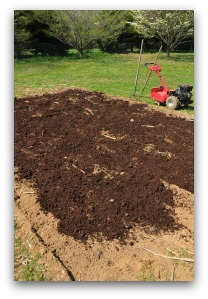 adding a layer of compost to vegetable garden