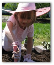young girl digging in a garden with a hand trowel